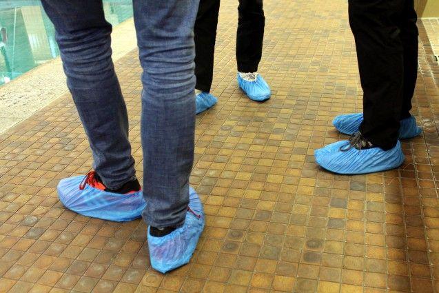 Dann geht es los. Doch mit Straßenschuhen kommt niemand ins Bad. Eine zuvorkommende Mitarbeiterin der Berliner Bäder-Betriebe verteilt beherzt blaue Plastiküberzieher, die sich alle über die Schuhe stülpen müssen.