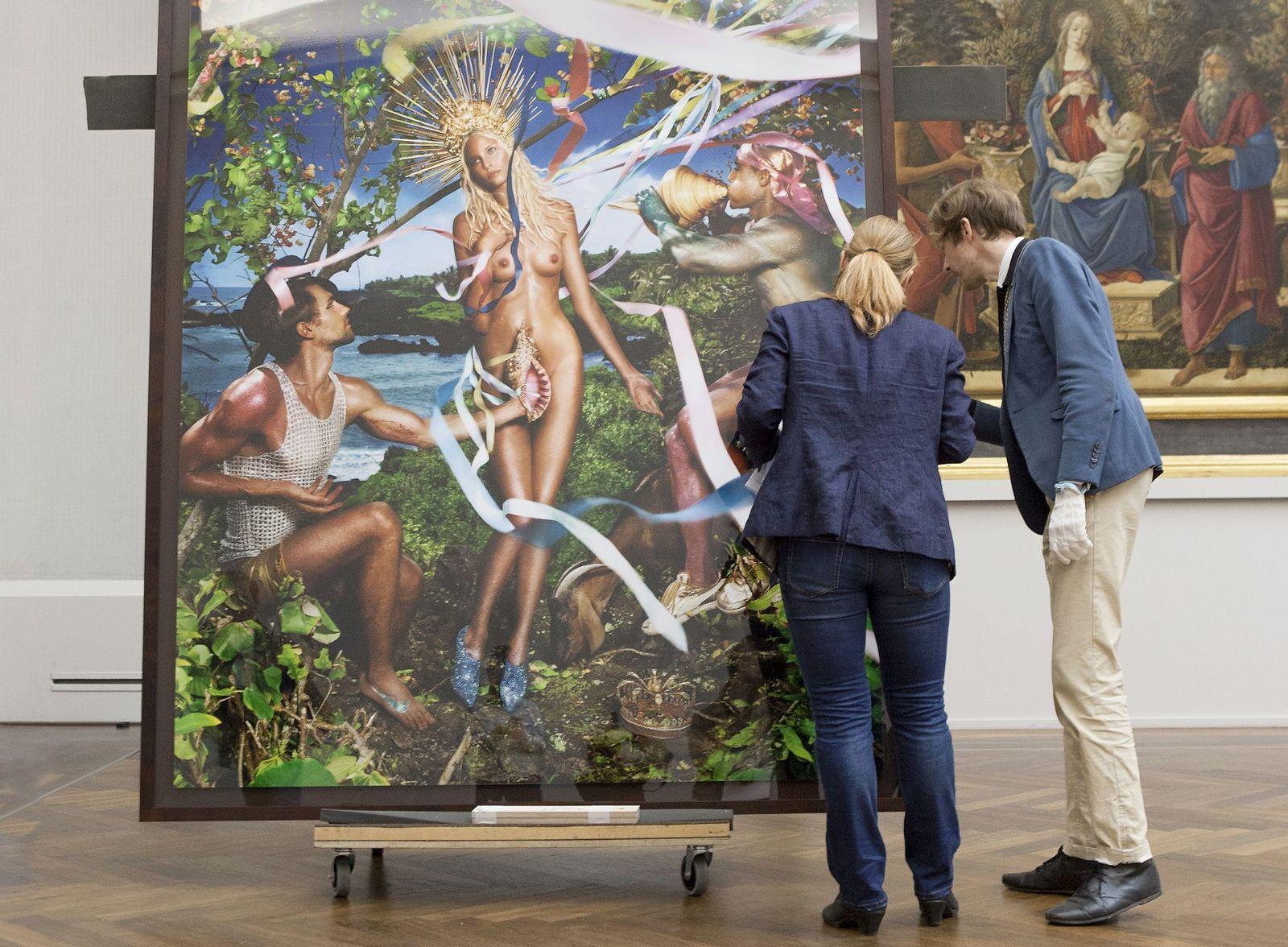 """Ruben Rebmann und die Foto-Restauratorin Stefanie Pfeifer kontrollieren den Zustand eines C-Prints von David LaChapelles """"Rebirth of Venus"""", das für die Ausstellung angeliefert wurde. Foto: Juliane Eirich"""