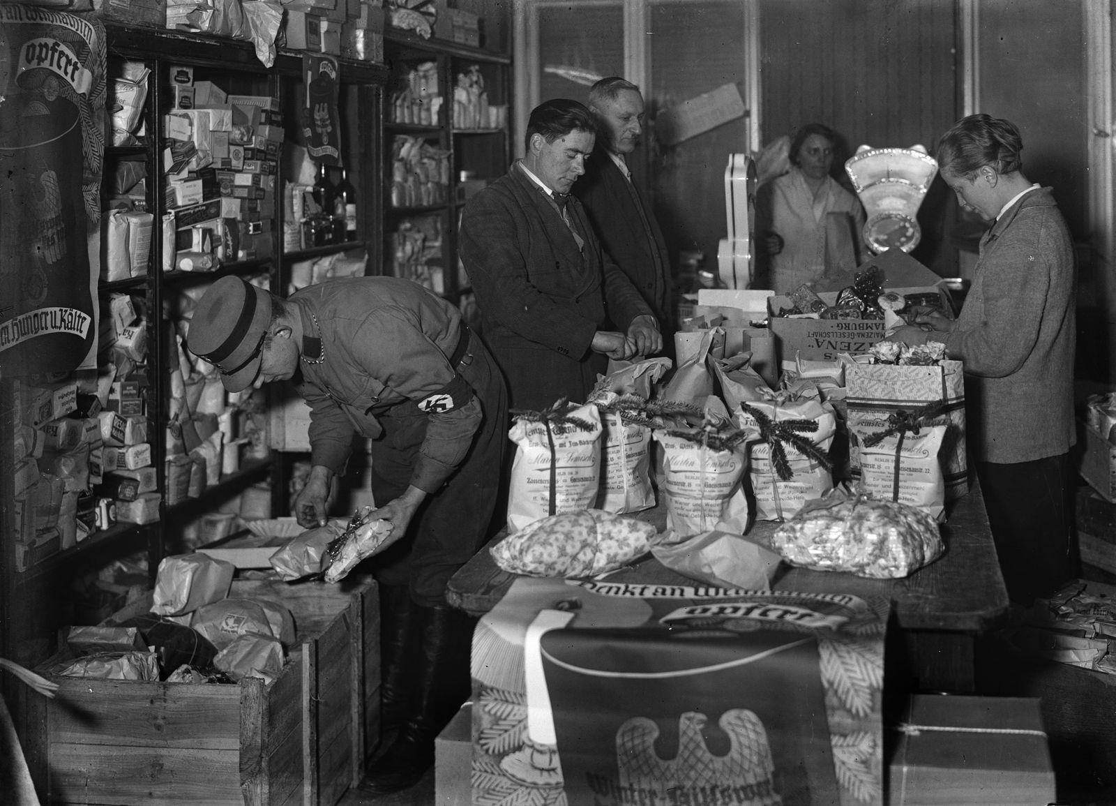 """Weihnachten unterm Hakenkreuz: """"Die bei der Ortsgruppe Gneisenau der NS-Volkswohlfahrt eingegangenen Pfundspenden werden zu Weihnachtspaketen für Bedürftige zusammengestellt (20.12.1933)."""" (c) bpk / Kunstbibliothek, SMB, Photothek Willy Römer / Willy Römer"""