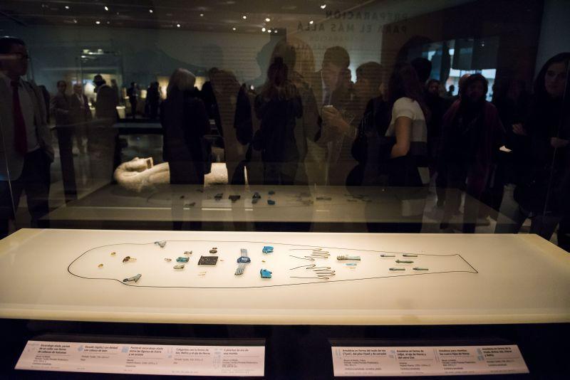 """Raum """"Jenseits"""" während der Eröffnungsfeier. Im Vordergrund die Umrisszeichnung einer Mumie mit darauf platzierten Amuletten und Goldauflagen.   © Centro Cultural La Moneda"""