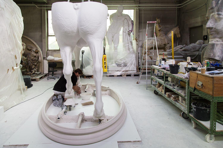 Mitarbeiter Jan Bürgel unter einem Teil des Pferdekörpers - das Bild verdeutlich die enorme Größe der Skulptur. Foto: Fabian Fröhlich
