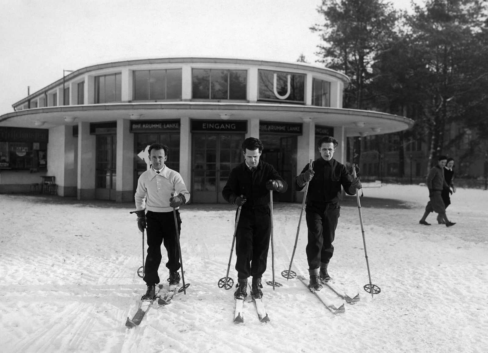 """""""Drei Skifahrer fahren direkt vom U-Bahnhof Krumme Lanke in das Skigebiet im Grunewald"""", 1931 © bpk / Kunstbibliothek, SMB / Willy Römer"""