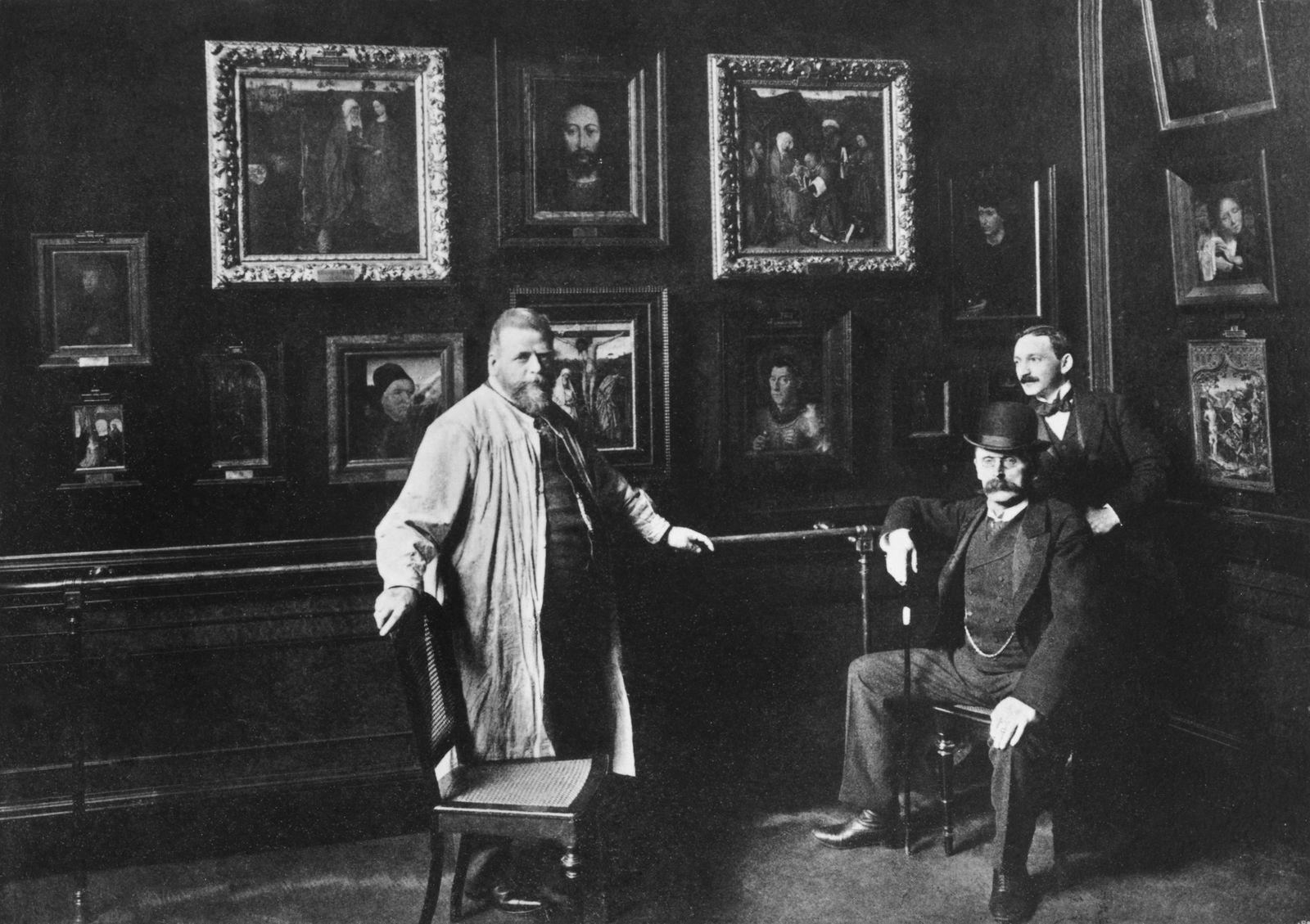 Wilhelm Bode (sitzend) mit Alois Hauser (links) und Max Friedländer in der Galerie im Kaiser-Friedrich-Museum (um 1900). Copyright: bpk / Zentralarchiv, Staatliche Museen zu Berlin