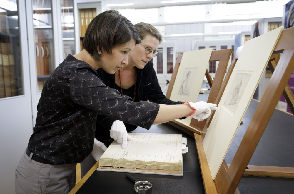 Curator Anna Pfäfflin (left) and provenance researcher Hanna Strzoda are comparing Johann Adam Klein's drawing with the associated entry of the inventory book. ©SPK/photothek.net/Thomas Köhler