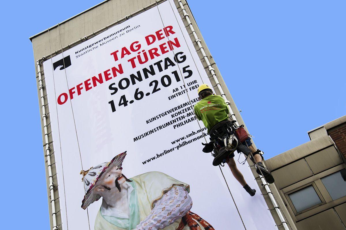 Montage des Banners zum Tag der offenen Türen an der Fassade des Kunstgewerbemuseums. Foto: Fabian Fröhlich