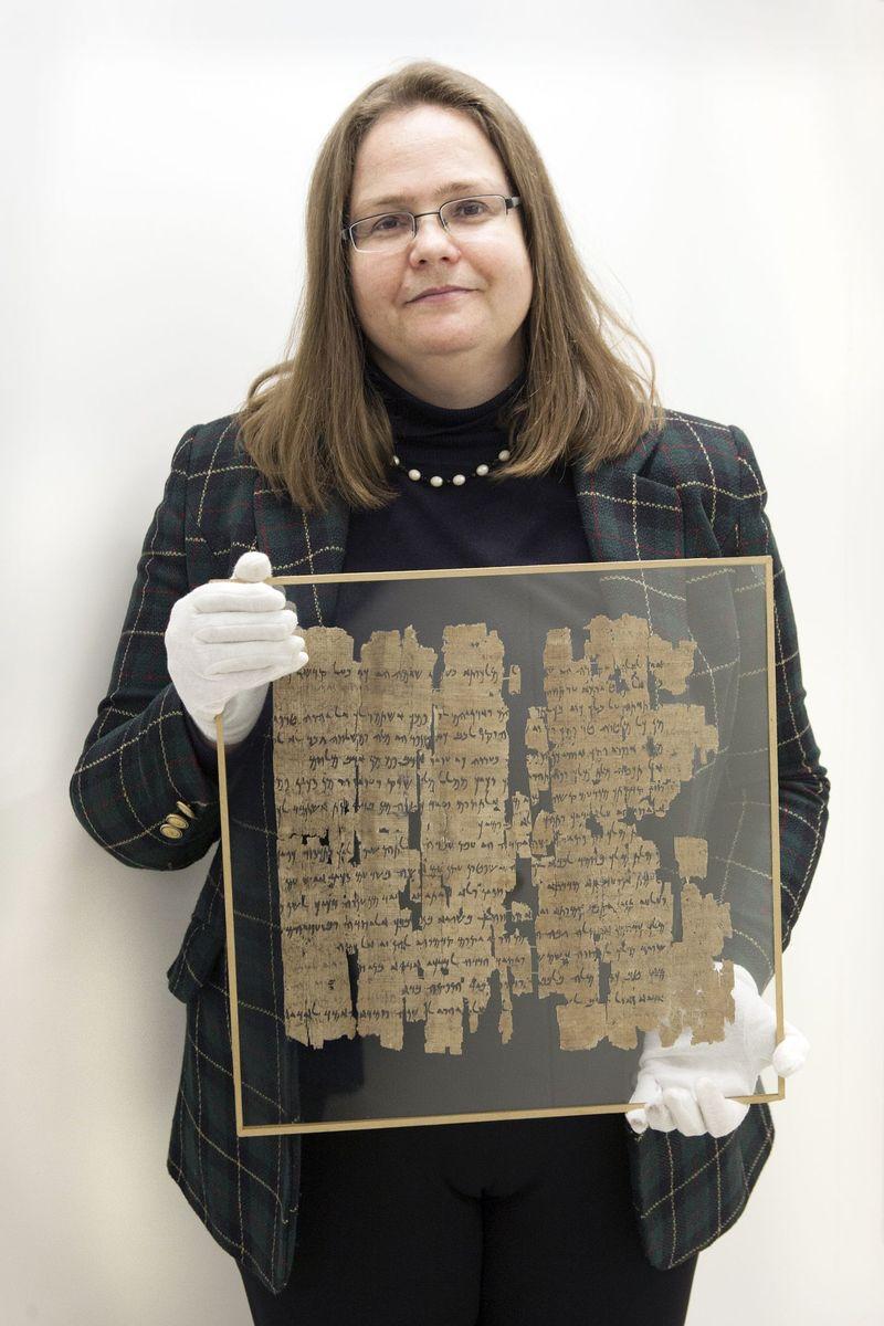 Verena Lepper zeigt einen in Glas gefassten Papyrus von der Nilinsel Elephantine, im Depot des Archäologischen Zentrums (c) Staatliche Museen zu Berlin / Juliane Eirich