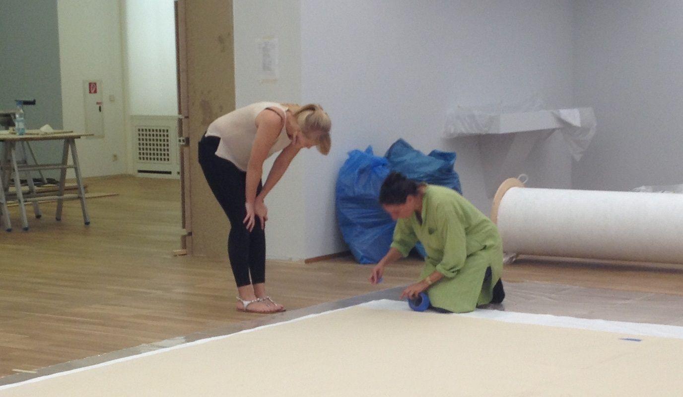 Restauratorin Hana Streicher und Praktikantin Theresa Weidt markieren die Ecken des Gemäldes für die Positionierung des Rahmens. Foto: Marie Förster, Nationalgalerie