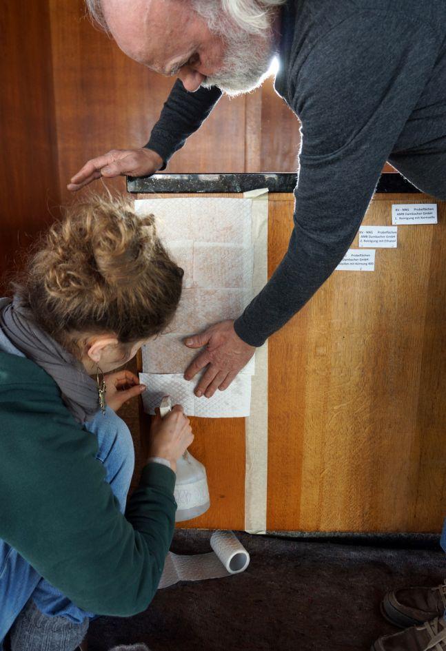 Der Holzrestaurator Wolfgang Dammbacher bringt Testanstriche auf dem Tresen für die Bemusterung auf. Foto: BBR/ProDenkmal